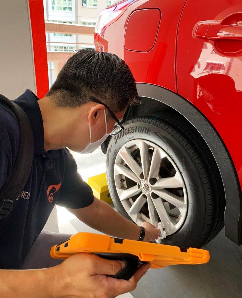 An AutoApp Service Ambassador checks the tyres on a customer's car