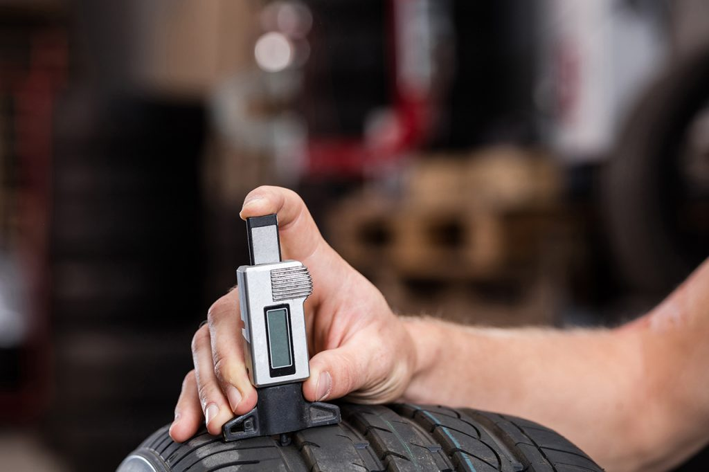 checking tyre tread depth with a digital gauge
